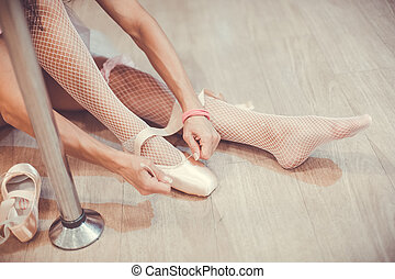 Close-up shot of a ballerina taking off the ballet shoes...