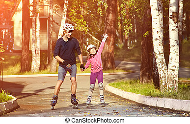 two people rollerblade - Dad with little daughter on the...