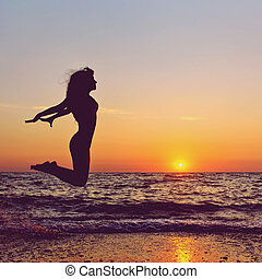 woman at sunset - silhouette of a happy woman jumping on a...