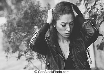 Depressed woman deep in thought outdoors