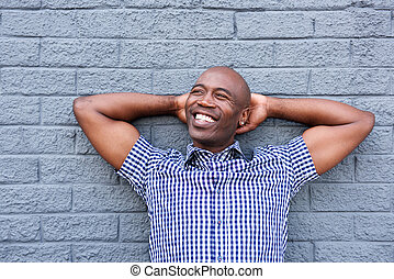Relaxing man with hands behind head