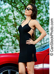 pleasure - Attractive young woman near the red sports car...
