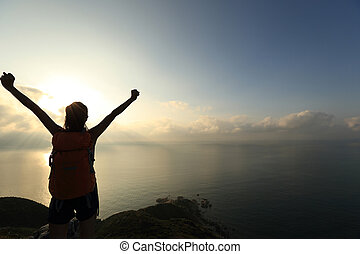 cheering young woman backpacker at sunrise seaside mountain...