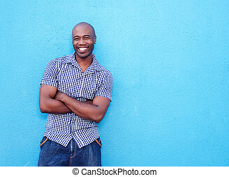 Handsome black man smiling with arms crossed - Portrait of...