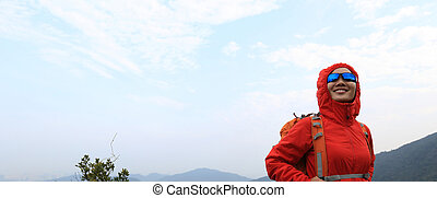 young woman backpacker hiking at mountain peak