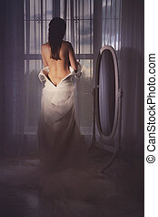 Bride takes off a wedding gown
