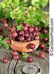 Red gooseberries in wooden bowl on country table