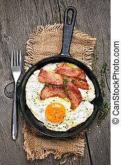Fried eggs and bacon in frying pan on wooden background