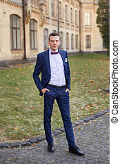 the groom in a blue suit and bow tie posing in the photo -...