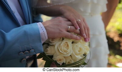 Hands of the bride and groom - closeup of bride and groom,...