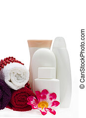White bottle, flower and beads with towels
