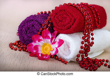 White and red towel around beads and flowers on a beige...