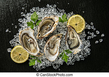Oysters served on stone plate with ice drift and lemon
