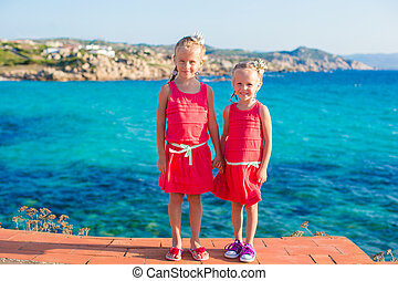 Adorable little girls at tropical beach during summer...