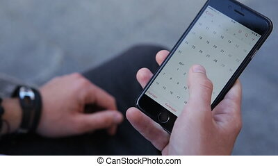 Close-up male hands scrolling screen on smartphone. Person...