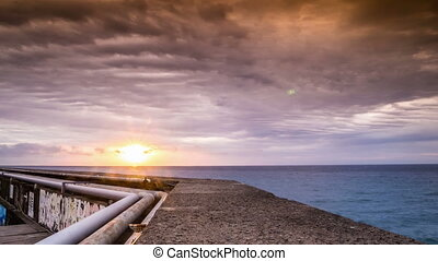 People walking on jetty at sunrise, Funchal, Madeira,...