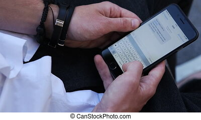 -up male hands texting. Using mobile device for making a...