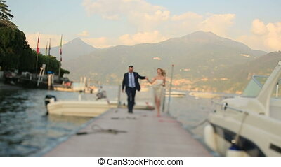 Bride and Groom Running Along the Pier - Bride and groom...