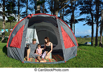 Young family camping in a tent outdoors