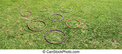 Nine 9 hula hoops on a green grass Abstract background