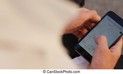 Close-up of young male hands zooming maps on smartphone to...