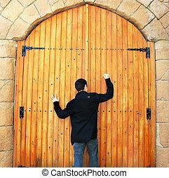 Teen knocking door - Teen knocking wooden old door in...