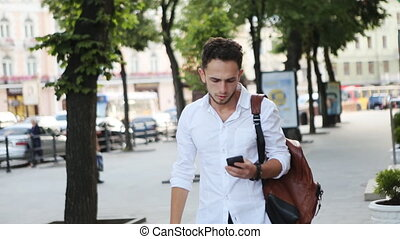 Young male in his 20s moving towards the street with smartphone in his hand and receiving a message