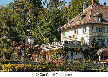 Ancient building at Lake Geneva, Switzerland with Garden on Side