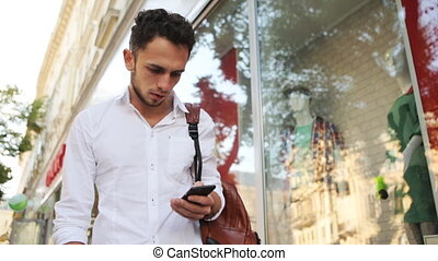 Attractive guy in a hurry texting on his mobile phone on the...