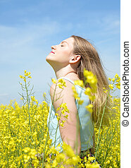 woman on blooming rapeseed field - Young happy woman on...