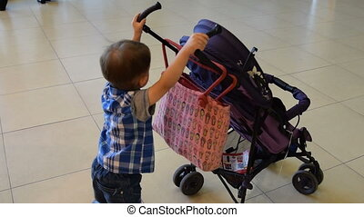 Child with baby carriage - Cute little boy rolling empty...