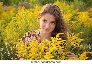 long-haired teen girl in grass during sunset