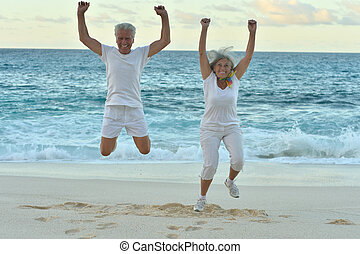 Senior couple jumping on seashore - Happy Senior couple...