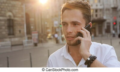 Attractive guy have a businness talk on the phone. Man...