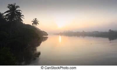 Early sunrise over foggy river