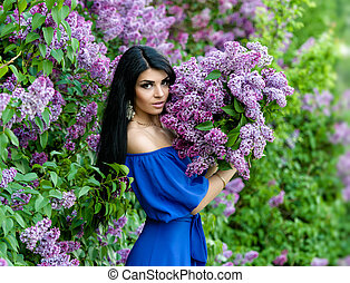 Beautiful smiling young woman with lilac flowers bouquet