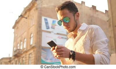 Young man worn blue mirror sunglasses typing a message on...