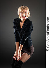 sexual blond woman in short skirt . Black background.