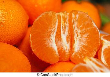 fresh peeled tangerine segments close up on a background of orange mandarins