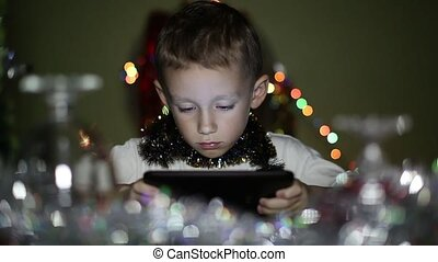 boy playing on the tablet in the New Years Eve - boy playing...