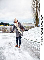 Pretty, young woman having troubles walking on an icy,...