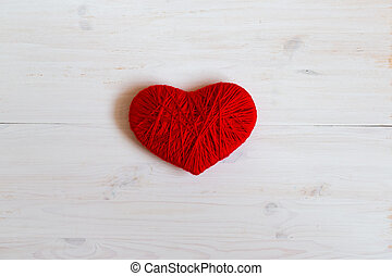 Red heart shape made from wool on white wooden background...