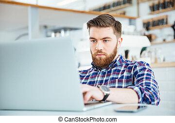 Man using laptop computer in cafe - Man using laptop...