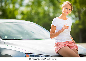 Young woman standing by her new car, having a refreshing...