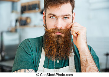 Handsome man with beard in white apron touching his...