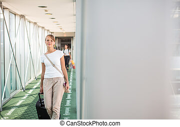 Portrait of a young woman in the boarding bridge, boarding an aircraft