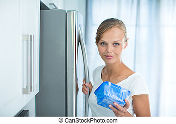 Is this still fine? Pretty, young woman in her kitchen by the fridge