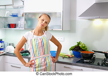 Portrait of a young woman wearing an apron, standing with a confident attitude in her modern kitchen