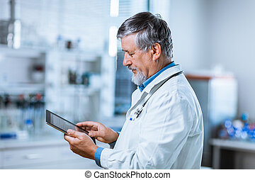 Senior doctor using his tablet computer at work color toned...