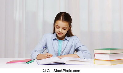 school girl writing math task to notepad - education,...
